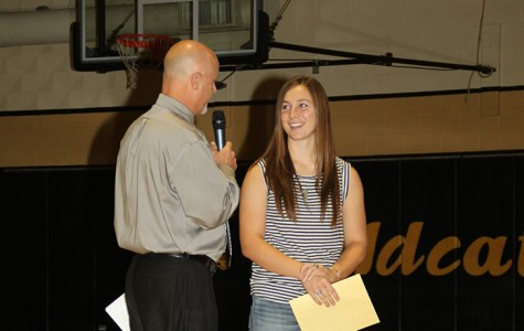 Senior Morgan Knobloch receives All-State Journalism staff award from Principal Vance Morris at the first day of school assembly.