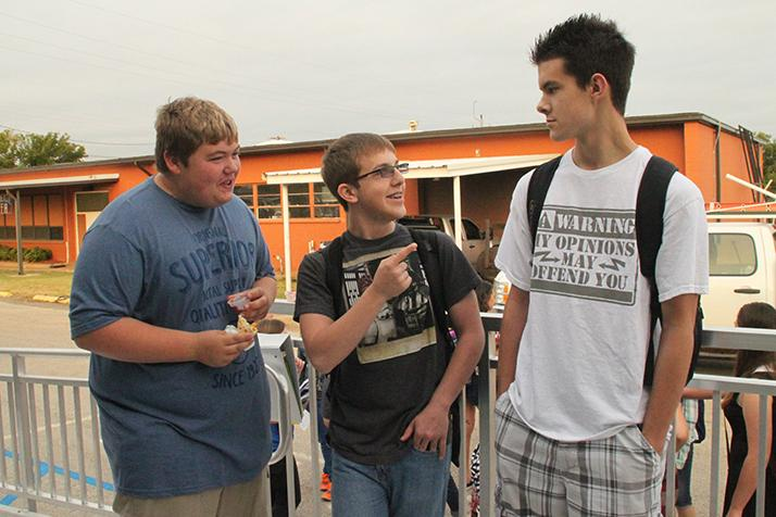 Senior Keith Tweed chats with juniors Guy Richardson and Toby Crowley outside the portable building before school.