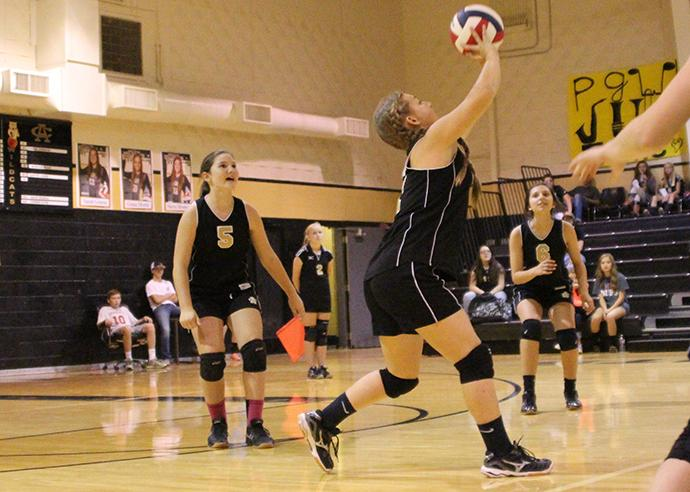 Eighth grader Breanna Howard watches teammate Lindy Reid push the ball over the net.