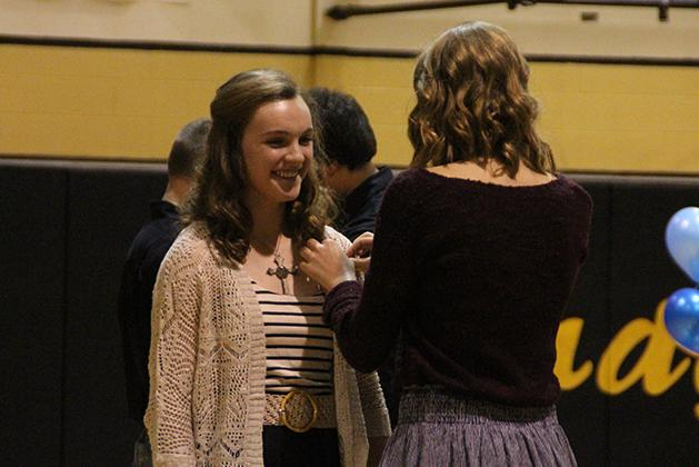Senior Taylor Sims pins sophomore Kennedy Huseman with the emblem of the National Honor Society.