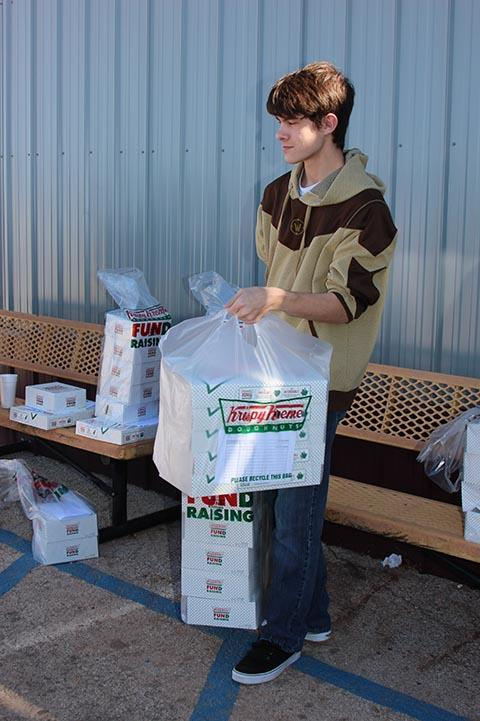 Junior Toby Crowley picks up his donuts to distribute.