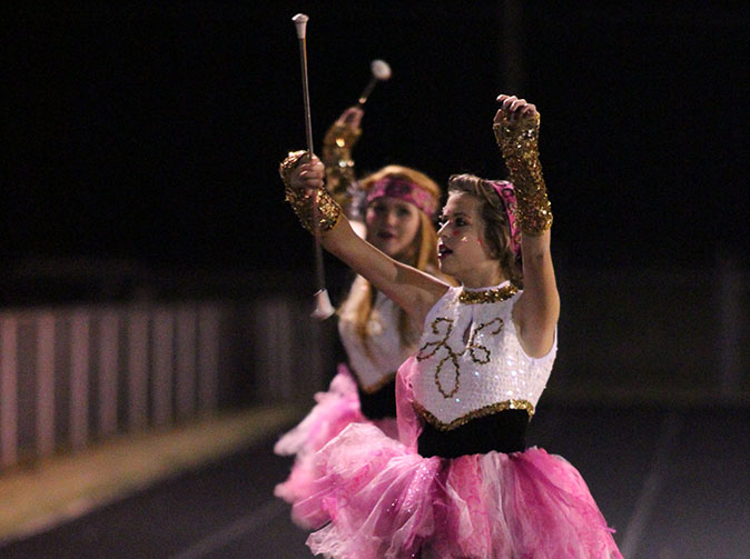 Eighth grader Morgan Veitenheimer and senior Bobbi Loran perform their routine at the pink out football game last fall.