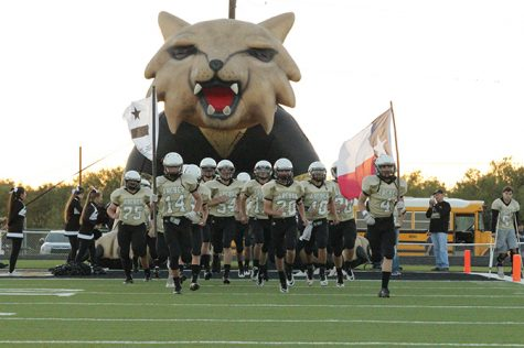The varsity football team runs out of the tunnel.