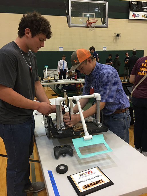Junior+Clay+McCasland+and+sophomore+Blake+Dunkel+make+some+final+adjustments+to+their+team%27s+robot+before+the+UIL+robotics+competition.+The+team+place+sixth+at+the+competition+and+will+be+advancing+to+state+in+December+