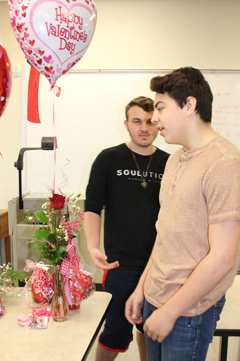 Member Bradley Anderson and co-vice president Brian De La Rosa discuss during FCCLA's valentine fundraiser. The chapter will no longer be selling valentine items through Millwright.