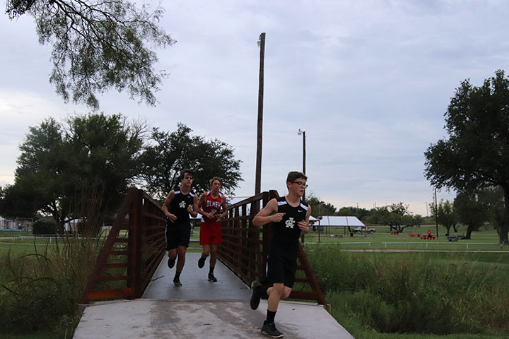 Picture of two Archer City Cross Country members running at a meet