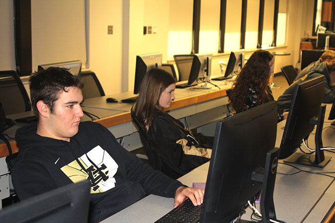 Juniors Jack Herring, Breanna Howard and Avery Williams  work on their college history assignment. for this online, dual credit course, they experience college-level curriculum.
