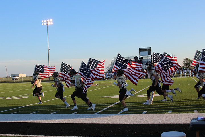 The+Wildcat+varsity+football+team+runs+on+to+the+field+carrying+American+flags.+