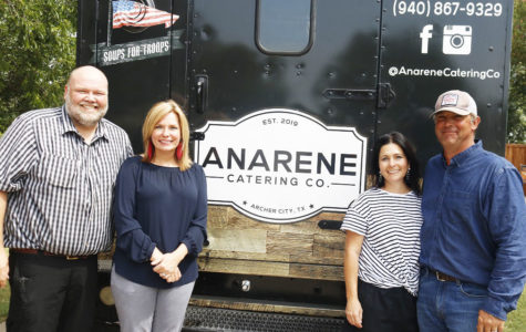 The owners of the food truck pose with their company logo