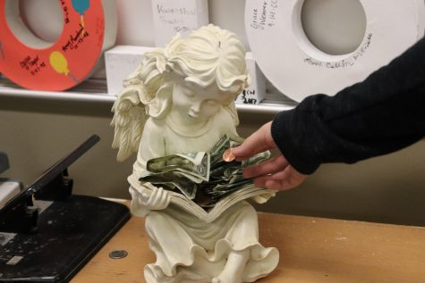 A student places a penny on the angel for good luck.