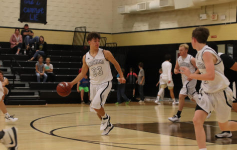 Junior Karlis Bergs dribbles the ball down the floor.