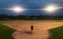 Coach Mallory Mooney looks out over the empty Ladycat softball field during the UIL suspension.