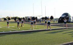 The cheerleaders perform the school song.